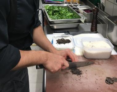 Le Chef Sébastien Guerra des Fourneaux du Manège découpant des truffes noirs du Périgord.